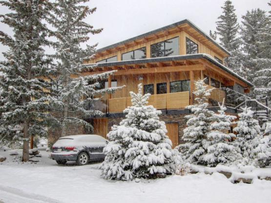 modern mountain timber home in canmore during winter