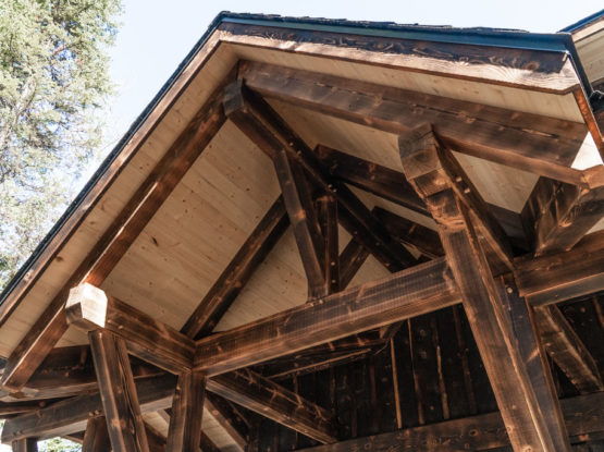 dark exterior timber frame rafters and brackets over a deck