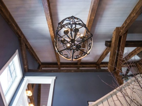 long timber beams over hallway with a big chandelier
