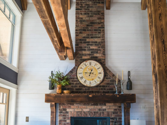 brick fire place with wooden mantel and timberframe beams