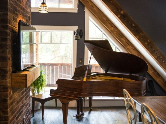 big piano in a living room corner under timber beams